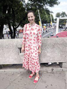 Felicitas steht mit einem langen weißen Kleid mit roten Blumen auf einem Gehsteig und grinst in die Kamera.