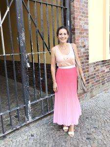 Regina steht in einem langen pinken Rock vor einem Einfahrtstor und strahlt.