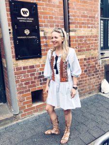 Renke steht vor einer braunen Backsteinmauer und lacht.