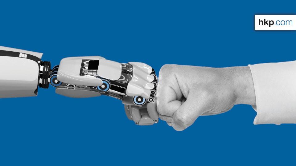 Faust an Faust: Eine Roboter- und eine Menschenhand - KI und natürliche Intelligenz müssen ein Team bilden.